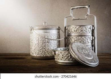 metal Tiffin carrier, thai food carrier on wooden table background.vintage color toned image