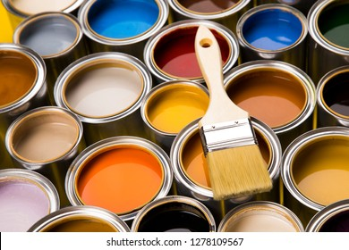 Metal tin cans with color paint and paintbrush