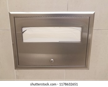 metal toilet seat paper dispenser on bathroom tile wall