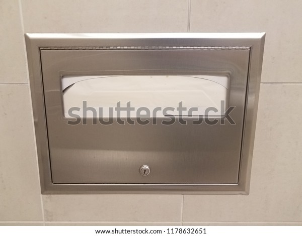 metal toilet seat paper dispenser on bathroom tile wall