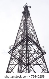 Metal tower with various communication antennas isolated on white.