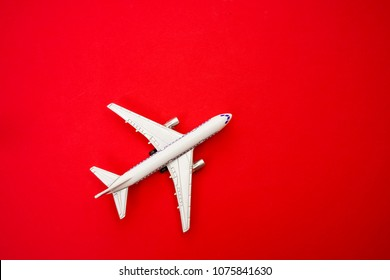 metal toy - airplane stand on red paper background. modern plane isolated  on red backdrop. travel and transportation idea.