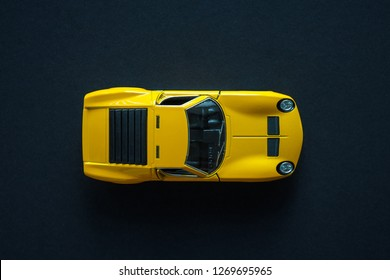 Metal toy sports car of yellow color. View from the top