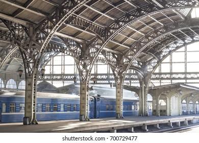 Metal train station with blue train. Empty platform in Saint Petersburg