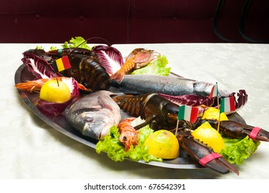 Metal tray of fish and crustaceans, lobster, sea bass, sea beam and shrimp with lemon salad and flags on toothpick in Italian restaurant dish for dinner
