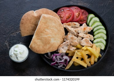 Metal tray with greek traditional chicken gyro, pitas, fresh vegetables and french fries, studio shot