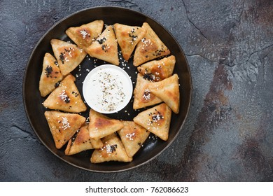 Metal tray with meat samosas on a weathered asphalt background, above view with space