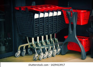 Metal trolleys at supermarket entrance. Cart for food and things as user's urge to consummation - in truck gaining more goods than in basket. Small secrets in Commerce for which hide big money concept