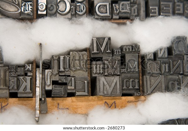 Metal type blocks, used for letterpress printing. Mixed type in a wooden tray with cotton wool packing.