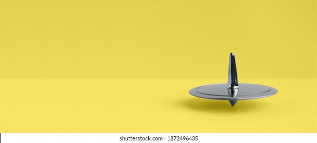Metal Ultimate Gray spinning-top rotation on a yellow Illuminating background, 2021, trendy color, rotation, color of the year