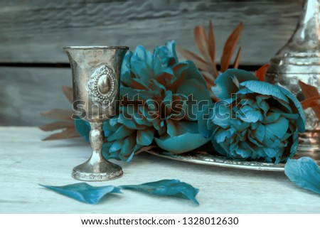 Metal vessel and blue peonies. Decorative composition.