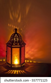 Metal Vintage Lantern lit by candle light with brilliant red and gold tones. Patterns of colored light on background/Metal Vintage Lantern background lit by candlelight with deep red and gold colors