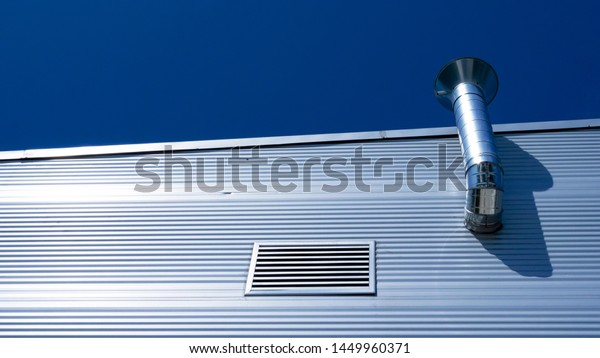 Metal wall panels with shiny metal chimney and ventilation pipe