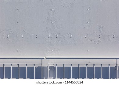 A metal wall with rivets, painted white, with railing, seen on an ocean ship.