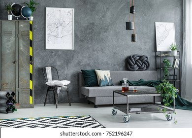 Metal wardrobe in grey living room interior with settee against dark concrete wall with city map posters