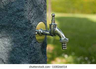 Metal water faucet on a stone