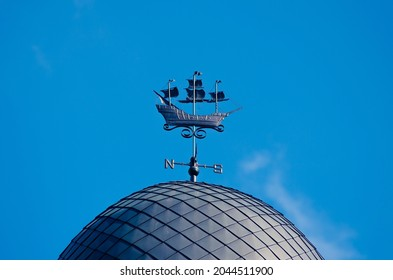 Metal weathervane in the form of a ship on the dome of the building against the blue sky