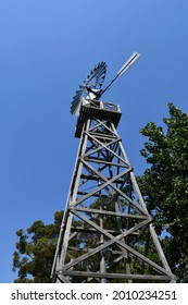 A metal wind mill is on a wooden frame. It is seen from below against a blue sky, surrounded by green trees. It is a typical Australian wind mill use for pumping water.