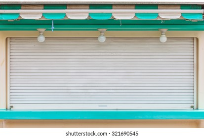 Metal window shutter closed at small shop