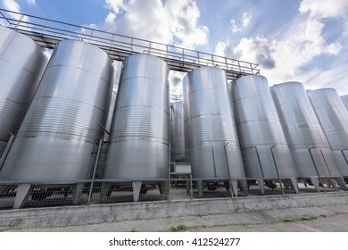 Metal wine barrels at a winery and blue sky with white clouds