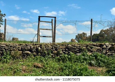 metal wire fence with wooden log door on stone wall