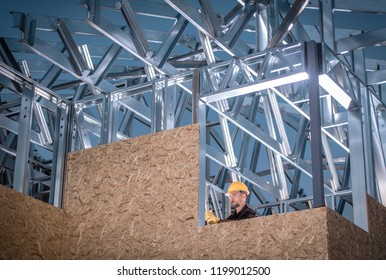 Metal and Wood Construction. Skeleton Frame of the Building and Caucasian Worker.