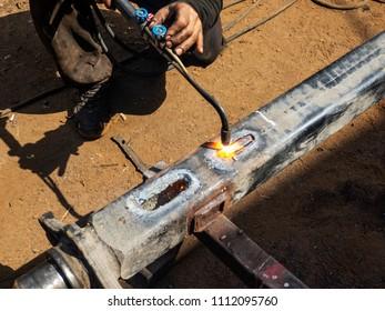Metal work. Man cuts a hole in a steel piece using gas welding