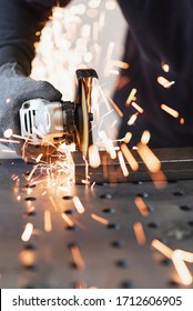 A metal worker cuts a rectangular metal pipe with an angle grinder