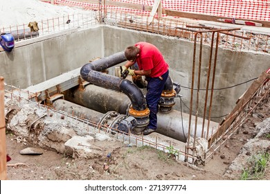 Metal worker is grinding weld on pipe junction completing a manhole for heating pipeline system.