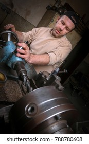 Metal worker shaping metal on lathe