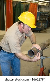Metal worker using a flexible ruler to measure pipe and mark it for cutting.  Authentic and accurate content depiction in accordance with industry code and safety standards.