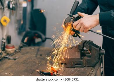 Metal worker using grinder.Selective focus and small depth of field.