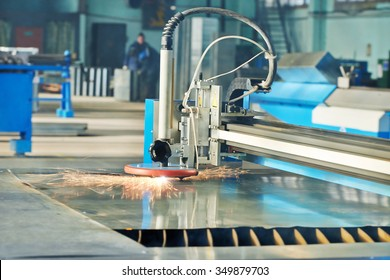 metal working. plasma laser cutting technology of flat sheet metal steel material processing with sparks. Authentic shooting in challenging conditions. Maybe little blurred.