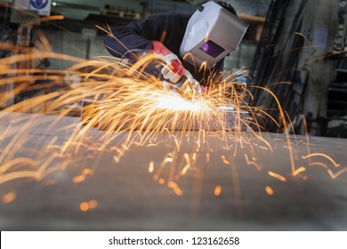 Metal wroker in a factory grinding with sparks
