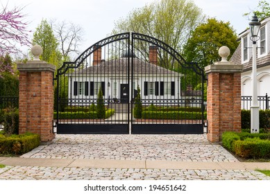 Metal wrought-iron gate and a house with landscaping
