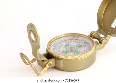 A metal, yellow compass on a white background