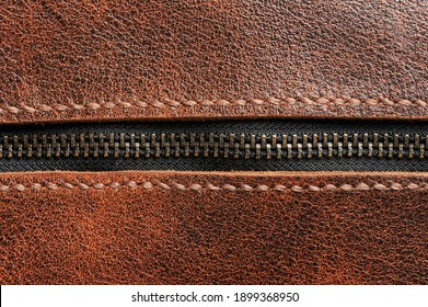 Metal zip closed lock. Zipper on brown leather surface macro close up view