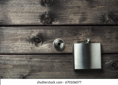Metall hip flask with cup on wooden backdrop