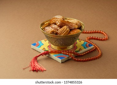 A metallic antique bowl filled with sweet arabic date fruits, placed along with Islamic prayer beads. Ramadan Kareem photo.
