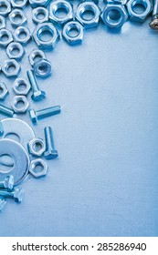 Metallic background with stainless screwbolts bolt washers and construction nuts repairing concept