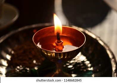 A metallic brass stand diya or lamp with a burning wick kept in a plate for pooja and aarti closeup