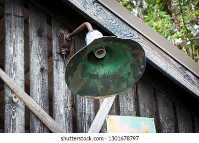 Metallic broken lamp in old wooden barn wall