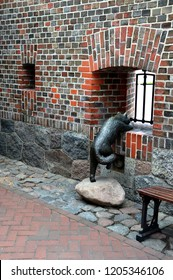 Metallic cat in the fortress looks out into the embrasure in the brick wall waiting for his master.