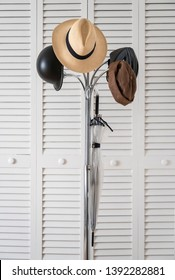 Metallic coat rack on which Panama hat are hung, bike helmets, hat and umbrella on a background of white doors with slats