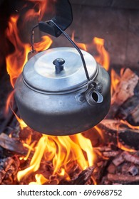Metallic coffee pot in campfire heat while trekking. Wood burning with flames beneath the pot.