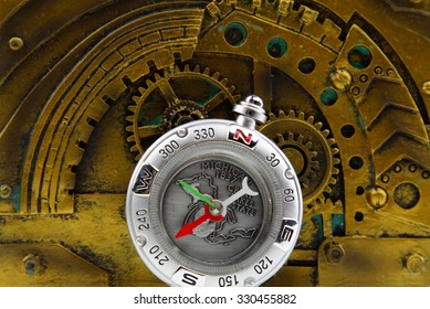 A metallic compass with gears in the background.