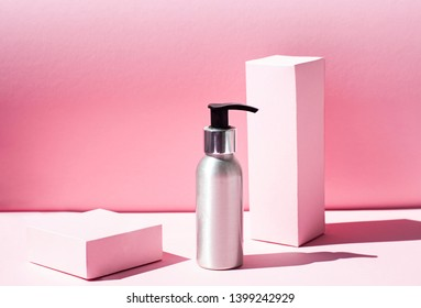 Metallic Cosmetic bottle on the pink background with harsh light. Close up
