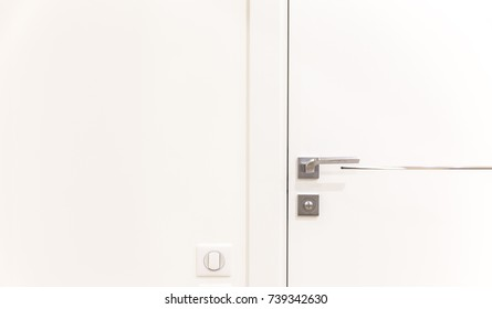 Metallic doorknob on a white modern door