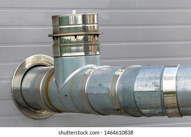 Metallic exhaust smoke pipes installed on house exterior wall.