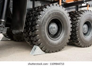 Metallic gray wheel chocks under the big black truck wheels